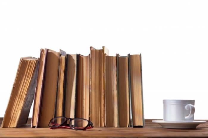 古い本とコーヒーカップとメガネの画像
