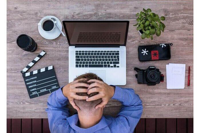 パソコンの前で頭をかかえる男性の画像